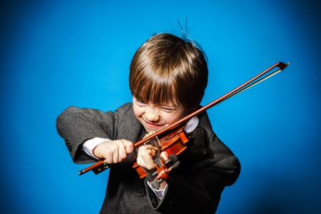 fiddlestick: Red-haired preschooler boy with violin, isolated on blue, music concept