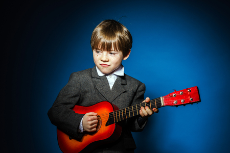 emphatic: Red-haired preschooler boy with ukalele, isolated on blue, music concept