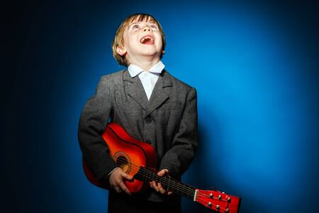 eloquent: Red-haired preschooler boy with ukalele, isolated on blue, music concept