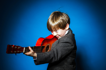 ruffian: Red-haired preschooler boy with ukalele, isolated on blue, music concept