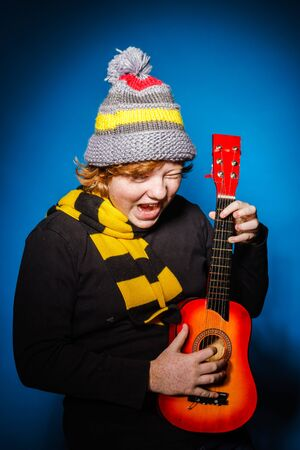 ruffian: Red-haired expressive teenage boy playing on ukalele, music concept