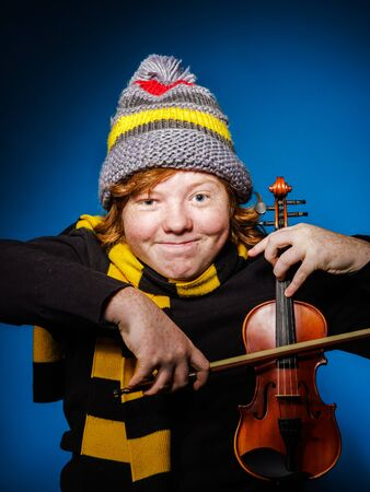 ruffian: Red-haired expressive teenage boy playing violin, funny concept, isolated on blue