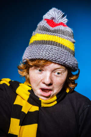 ruffian: Expressive teenage boy dressed in colorful hat close-up studio portrait, isolated