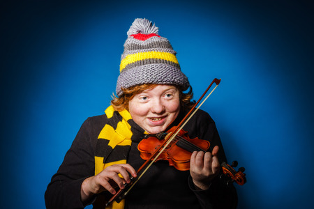 emphatic: Red-haired expressive teenage boy playing violin, funny concept, isolated on blue