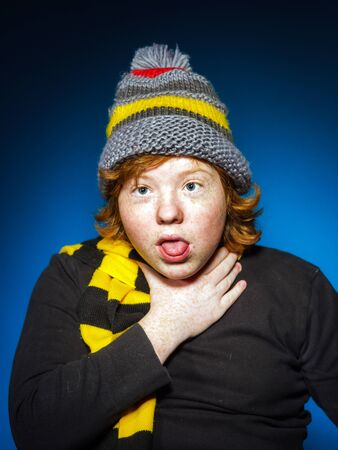 emphatic: Expressive teenage boy dressed in colorful hat close-up studio portrait, isolated