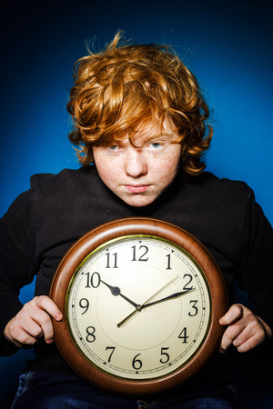 emphatic: Expressive red-haired teenage boy showing time on big clock, business and time concept
