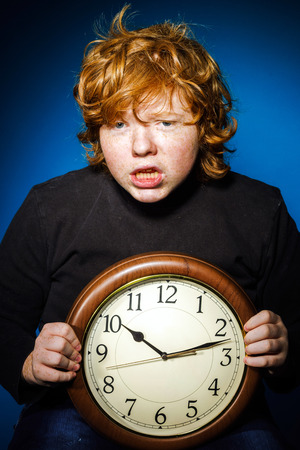 ruffian: Expressive red-haired teenage boy showing time on big clock, business and time concept