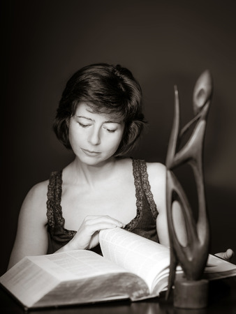 attentiveness: Young woman reading big book, concentration and attentiveness, isolated Stock Photo