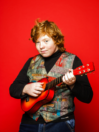 emphatic: Red-hair funny teenage boy playing little guitar, isolated on vivid red background