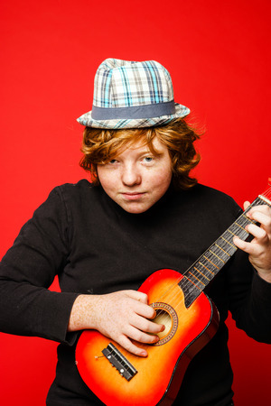 ruffian: Red-hair funny teenage boy playing little guitar, isolated on vivid red background