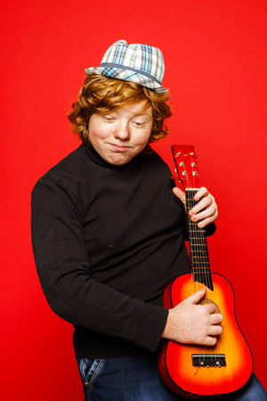 emphatic: Red-hair funny teenage boy playing little guitar, isolated on vivid red