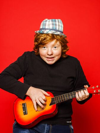 ruffian: Red-hair funny teenage boy playing little guitar, isolated on vivid red