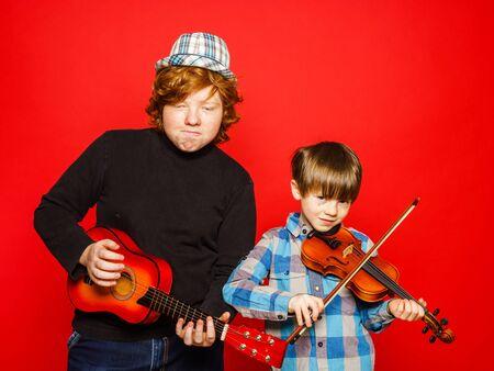 brothers playing: Dos hermanos divertidos rojo-pelo con m�sica, aislado en rojo