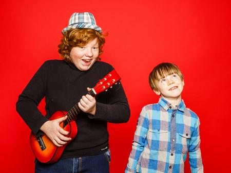 hermanos jugando: Dos hermanos divertidos rojo-pelo con m�sica, aislado en rojo