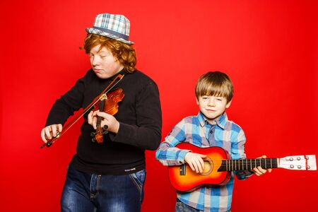 emphatic: Two funny red-hair brothers playing music, isolated on red Stock Photo