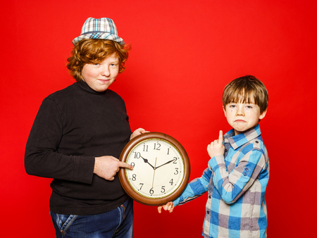 emphatic: Two red-hair brothers posing with big clock, isolated on red Stock Photo