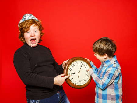 ruffian: Two red-hair brothers posing with big clock, isolated on red Stock Photo