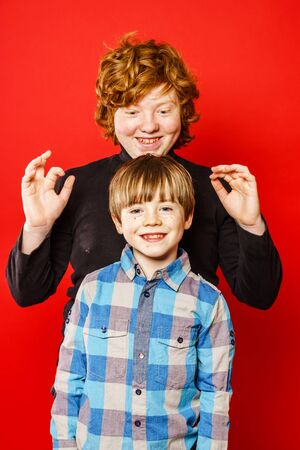 emphatic: Two expressive brothers studio portrait, red-haired boys isolated on red