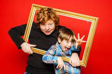 ruffian: Two expressive brothers studio portrait, red-haired boys isolated on red