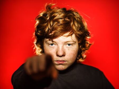 emphatic: Expressive red-haired teenage boy showing emotions in studio, isolated on red