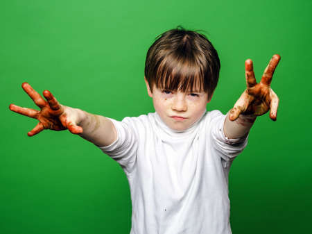 expressive: Expressive boy showing colorful hands after drawing, isolated on green