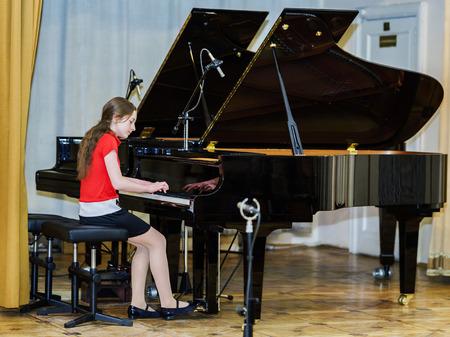 콘서트 홀에서 그랜드 피아노를 연주하는 십 대 소녀