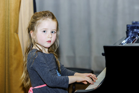 grand kid: Cute little girl playing grand piano in concert hall