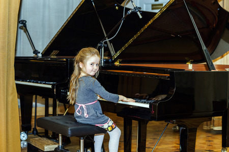 grand kids: Cute little girl playing grand piano in concert hall