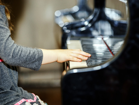 pianoforte: Cute little girl playing grand piano in concert hall