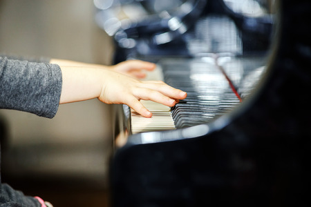 playing piano: Cute little girl playing grand piano in concert hall