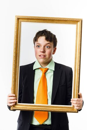 expressive: Expressive teenage boy posing with picture frame, isolated on white