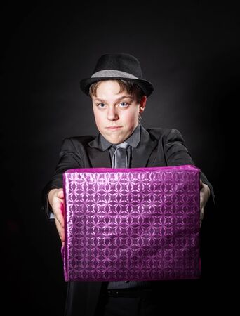 emphatic: Expressive teenage boy holding box with gift isolated on black