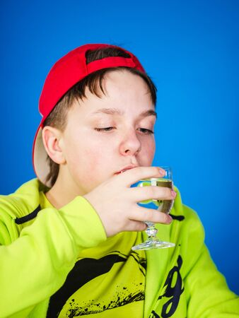 emphatic: Expressive teenage boy posing with glass of water, isolated on blue