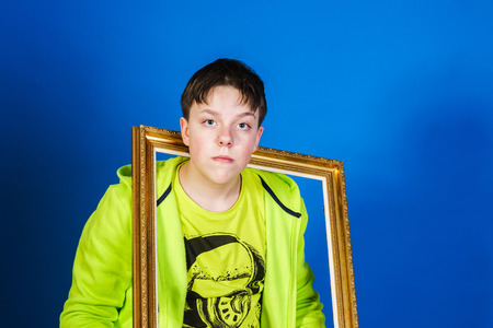 emphatic: Affective teenage boy posing with picture frame, isolated on blue background Stock Photo