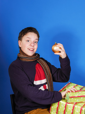 emphatic: Teenage boy posing with christmas gift boxes, isolated on blue background