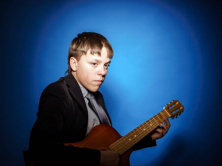 emphatic: Teenage boy posing with guitar, isolated on blue Stock Photo