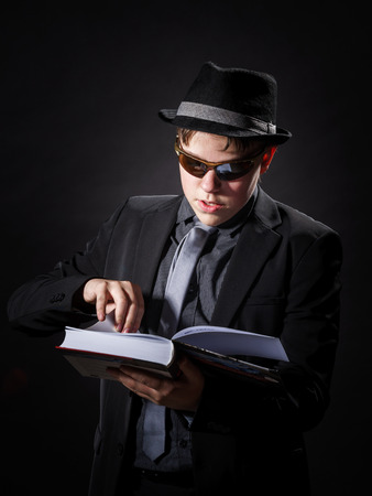 emphatic: Seriously teenage boy dressed in suit reading book, isolated on black