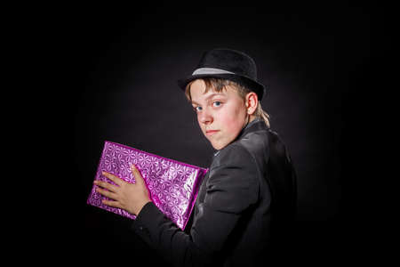 expressive: Expressive teenage boy holding box with gift isolated on black