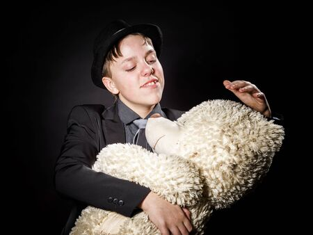 emphatic: Teenage boy dressed in suit with his old toy - teddy-bear, isolated on black