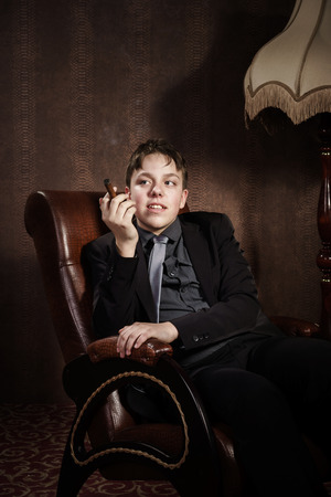 smoker: Young cigar smoker sitting in arm-chair, healthcare concept