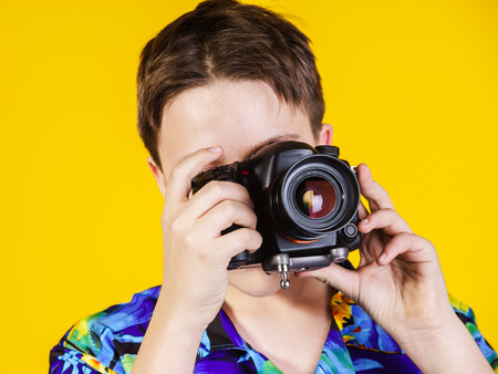 emphatic: Teenage boy posing with photo camera, isolated on yellow Stock Photo