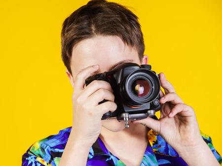 emphatic: Teenage boy posing with photo camera, isolated on yellow Stock Photo