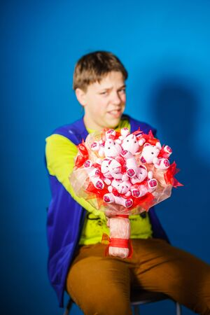 emphatic: Teenage boy posing with bouquet of flowers, isolted on blue Stock Photo