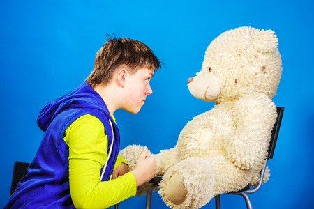 emphatic: Teenage boy with his old teddy-bear toy, isolated on blue