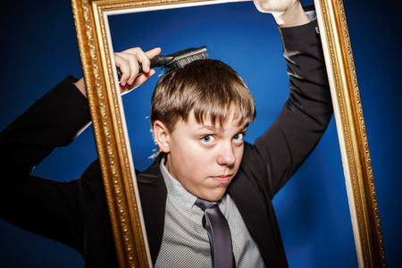 Teenage boy posing with picture frame, isolated on blue photo