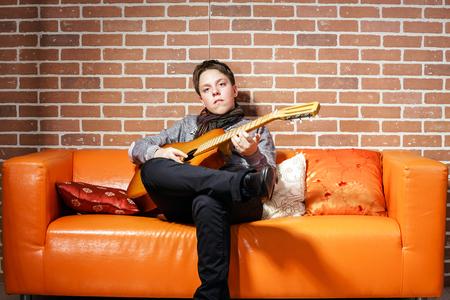 emphatic: Young teenage musician posing with guitar, studio portrait Stock Photo