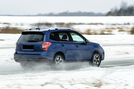 sputter: Powerful offroader car sliding by lake ice on winter sport trace