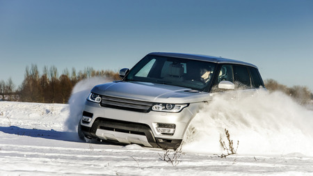 4x4: Powerful 4x4 offroader car running on snow field winter day, transport concept