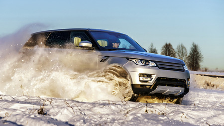 sputter: Powerful 4x4 offroader car running on snow field winter day, transport concept