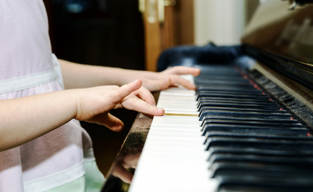 Girl's hands and piano keyboard close-up view, education concept Standard-Bild